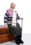 老妇人坐有藤茎的一个配件箱 免版税库存照片