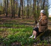 老妇人坐树桩 免版税库存照片
