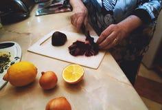 老妇人是烹调,切甜菜 免版税库存照片
