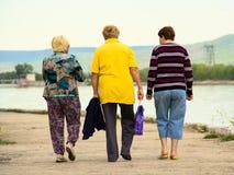 老妇人沿堤防走 库存图片