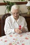 老妇人润滑坐在桌上的手奶油 图库摄影