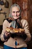 老妇人用自创曲奇饼 免版税图库摄影