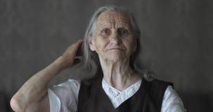 老妇人的特写镜头面孔有抚摸灰色头发的深皱痕的 影视素材