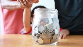 老妇人祖母的手给清楚的存钱罐的在白色背景隐喻挽救金钱的亚裔小女孩educat的 股票录像