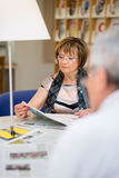 老妇人读取报纸在图书馆里 免版税图库摄影