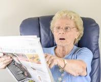 老妇人读取报纸 免版税库存图片