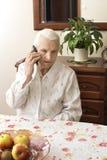 老妇人谈话在手机,当坐在一张桌上在客厅时 免版税库存图片