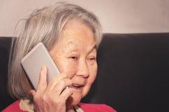 老妇人谈话愉快在电话 免版税库存照片