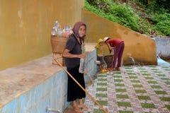 老妇人运载的水 库存图片