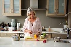 老妇人食物为一顿膳食做准备在厨房里 库存照片