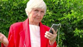 老妇人,震动的祖母 户外太阳天 红色夹克听的音乐的现代白种人老婆婆在耳机 股票视频