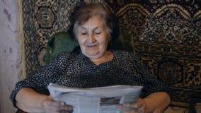 老妇人读书报纸在家