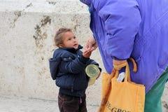 老妇人给斯科普里捐钱,马其顿的首都逗人喜爱的叫化子女孩街市  免版税库存照片