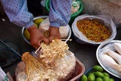 老妇人holdiing的火菇菌素velutipes的手 免版税库存照片