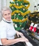 老婆婆微笑的钢琴作用 图库摄影