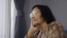 老孤独的妇女坐沙发在客厅 股票视频