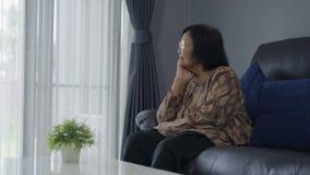 老孤独的妇女坐沙发在客厅 影视素材