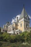 老宫殿,如此包围与在背景蓝色的绿叶 免版税库存照片