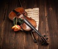 老小提琴、弓和乐谱与上升了 免版税库存照片