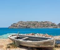 老小船在岸把流浪汉留在与海岛在背景 免版税库存照片