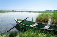 老小船在春天抓了与桨的油漆沿岸航行 免版税库存图片