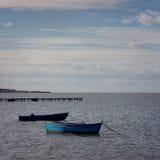 老小船在浪潮起伏的水域中 图库摄影