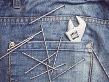 老工具和蓝色牛仔裤 免版税库存图片