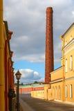 老工厂烟囱在城市 图库摄影