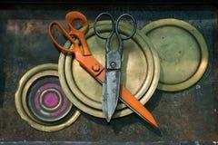老巨大的剪刀说谎在彼此顶部在铜中圈子的橙色和黑金属退了色在生锈的bac的黄色板材 免版税图库摄影