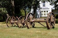老巨大的马车车轮在前面停放了一间农舍 免版税库存图片