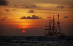 老帆船在日落的海 免版税库存照片
