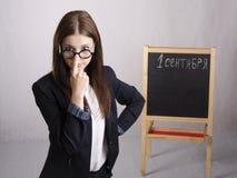 老师поправляющего眼镜的画象在他的鼻子和委员会的在背景中 免版税图库摄影