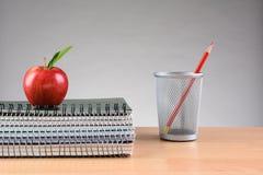 老师书桌笔记本苹果计算机铅笔杯 免版税库存照片