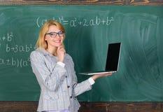 老师典雅的夫人有现代膝上型计算机冲浪的互联网黑板背景  库存照片