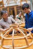 老师和一名学生木材加工的把工作在框架分类 免版税图库摄影