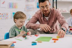 老师和可爱的学龄前儿童画象有雕刻图的彩色塑泥的在桌上 免版税库存照片