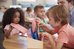 老师和学生与信件一起使用在蒙台梭利学校 图库摄影