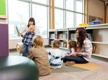 老师和学生在图书馆里 免版税库存照片