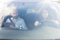 老师和学生在汽车推进测试期间 库存图片