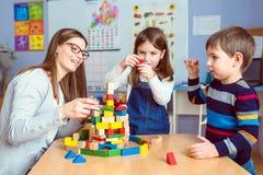 老师和孩子与五颜六色的大厦玩具块一起 图库摄影