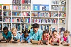 老师和孩子使用数字式片剂在图书馆里 免版税库存图片