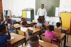 老师和孩子在一个教训期间在一所小学 免版税库存照片