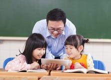 老师和孩子有数字式片剂或ipad的 免版税库存照片