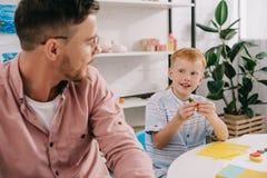 老师和红色头发学龄前儿童有雕刻图的彩色塑泥的在桌上 免版税图库摄影