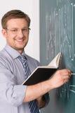 年轻老师和经典黑板背景 免版税图库摄影