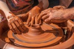 老师在一个转动的瓦器轮子的泥罐教雕刻 免版税图库摄影