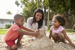 老师在使用与沙坑的孩子的蒙台梭利学校 免版税库存照片