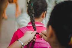 老师在回家前准备学生` s头发 免版税库存照片