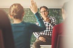 老师在教室递学生 库存图片