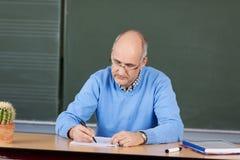 老师在他的书桌的文字笔记 库存照片